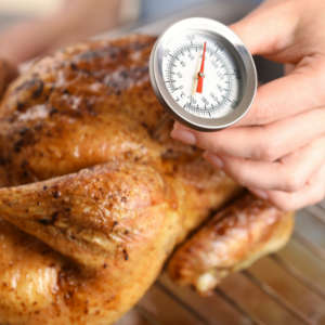 woman testing internal temperature of chicken with a meat thermometer