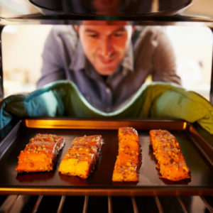 man placing salmon filets in the oven